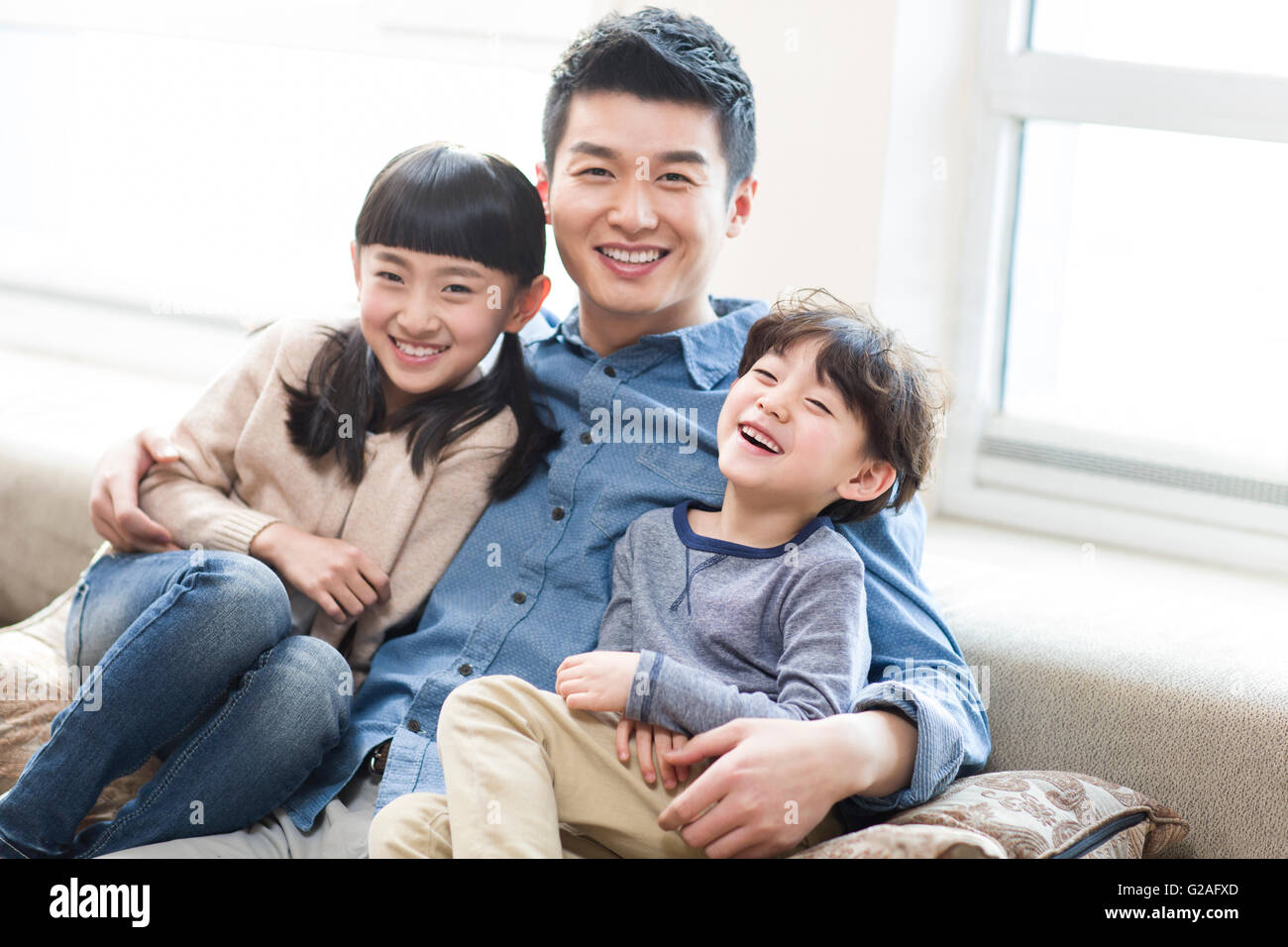 Happy young family resting in sofa Stock Photo