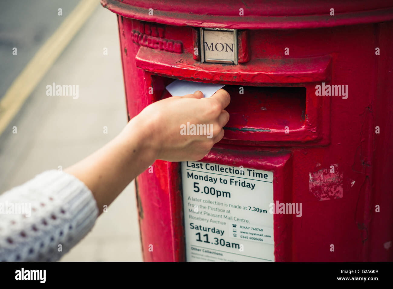 2 May 2015, London, United Kingdom - A female hand is posting a letter in a mail box belonging to Royal Mail - Stock Image