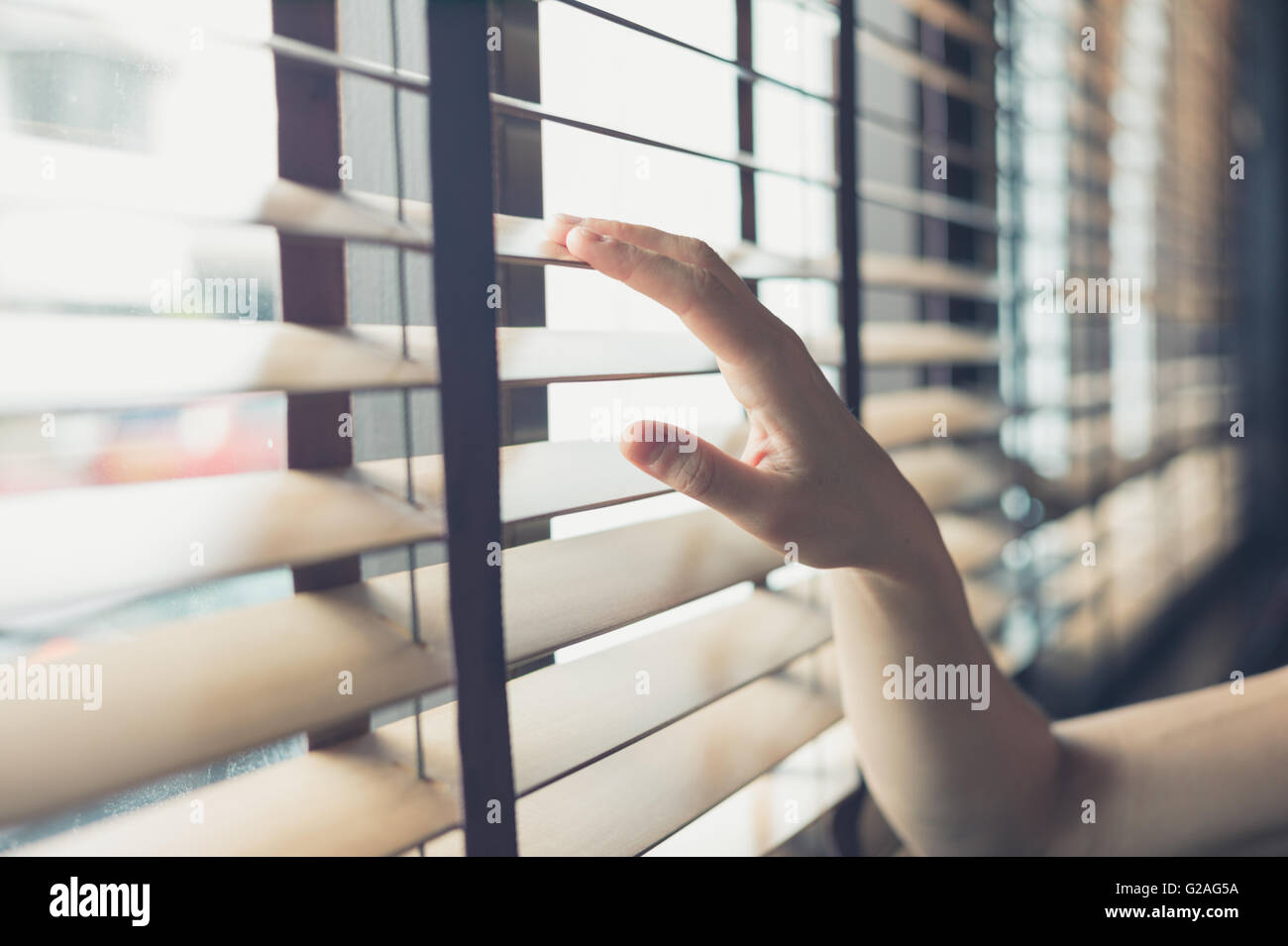 A young female hand is touching some venetian blinds by the window - Stock Image