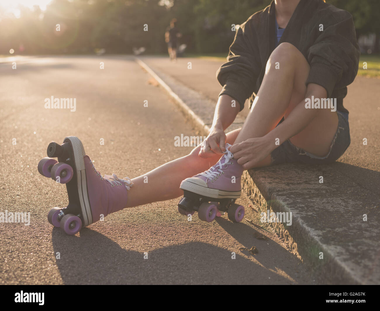 A young woman is sitting on the ground and is putting on roller skates in the park at sunset - Stock Image