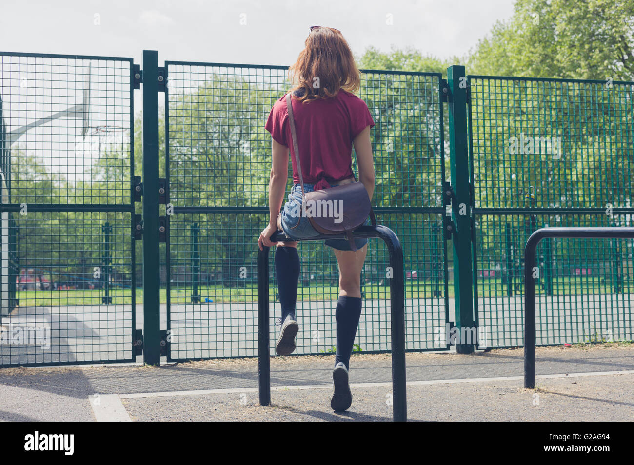 A young woman is sitting on a rail in a park outside a basketball court on a summer day - Stock Image
