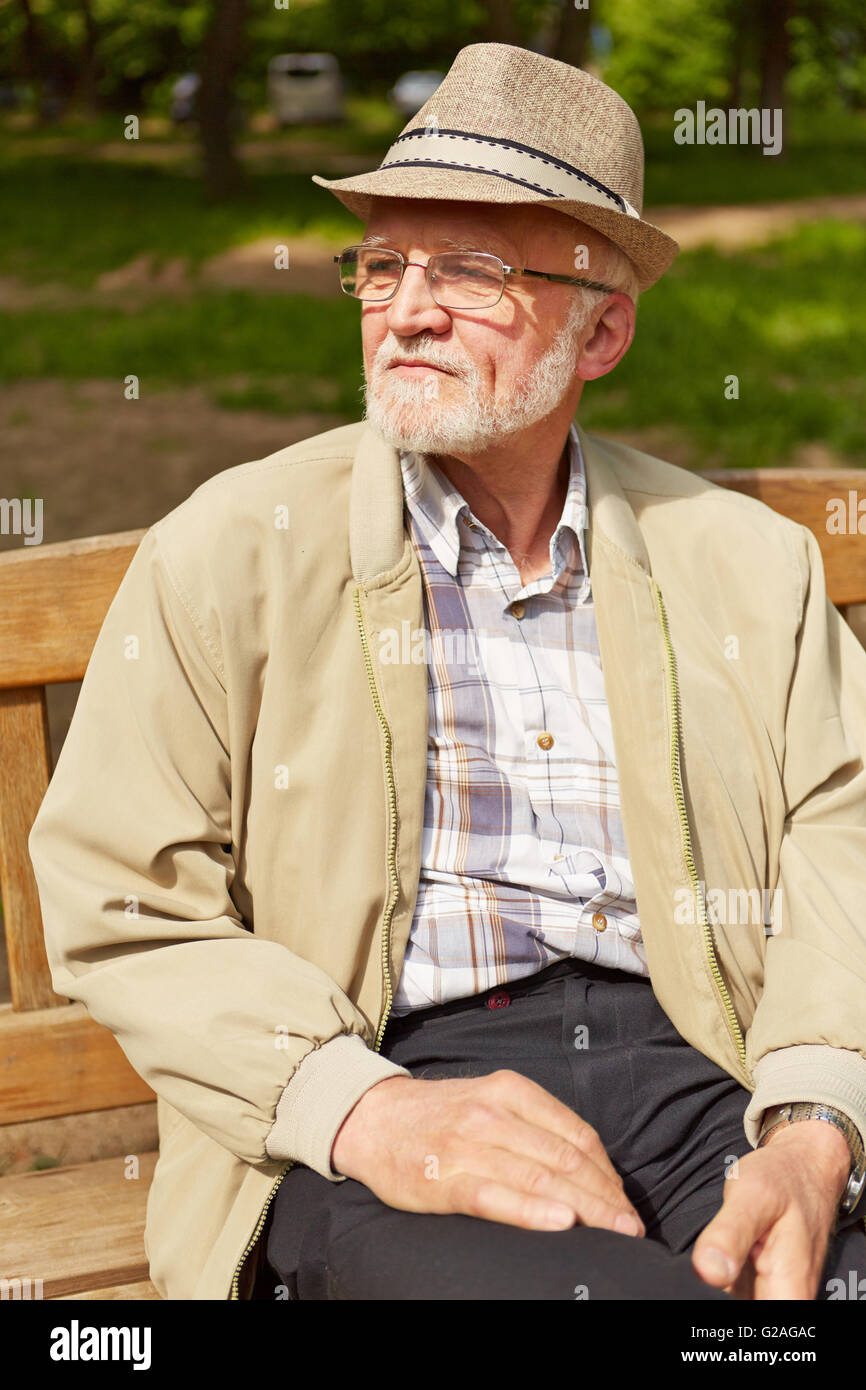 e01a1dc4008db Old man with hat and glasses sitting on park bench in summer Stock ...