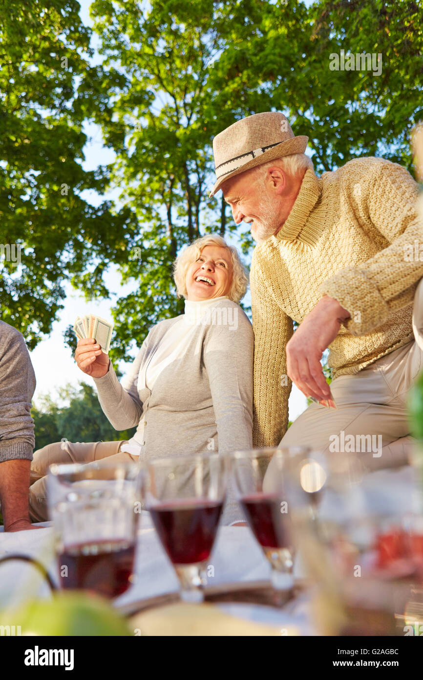 Happy senior people playing cards in a garden in summer - Stock Image