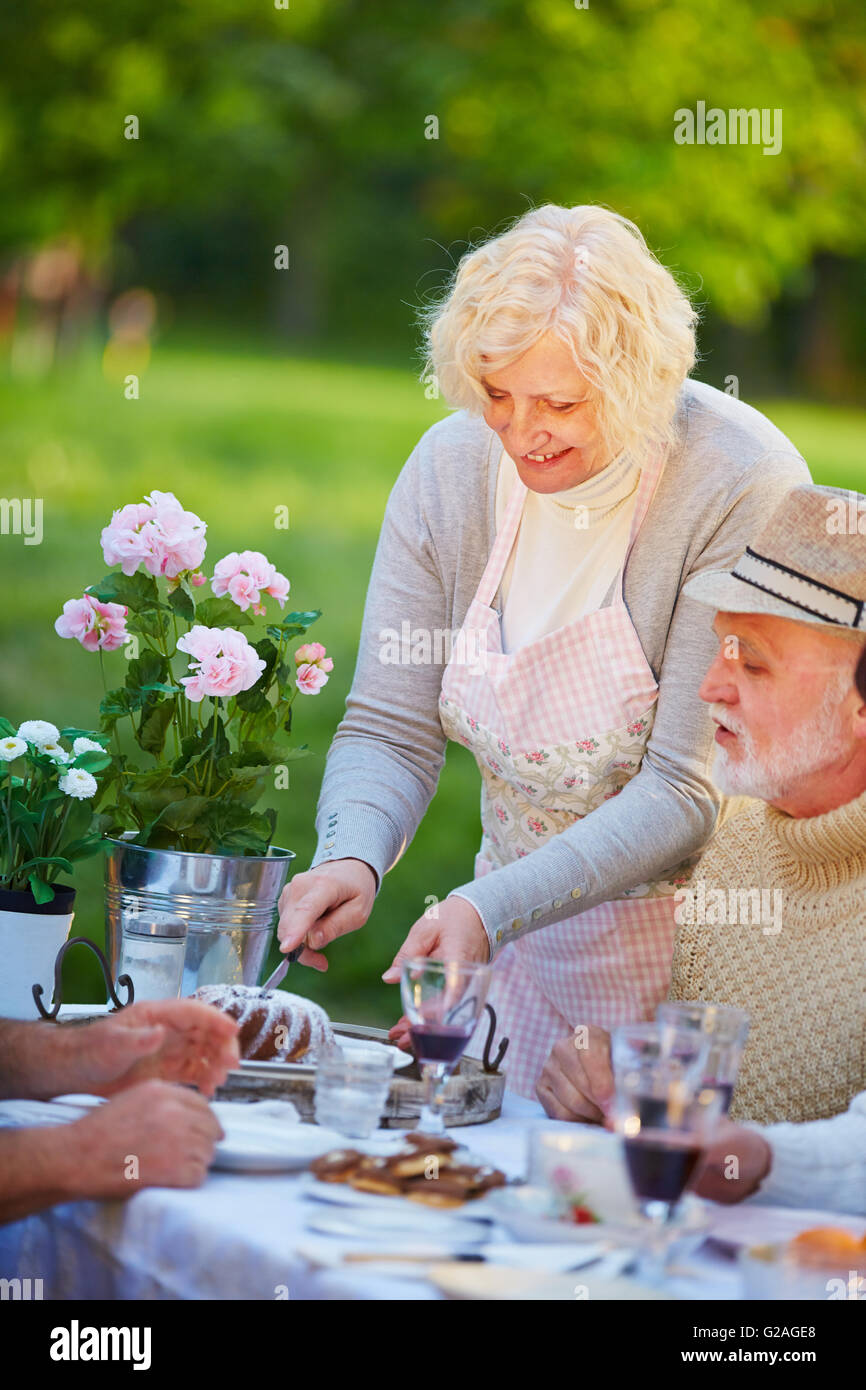 Senior woman serving ring cake at birthday party in a garden - Stock Image