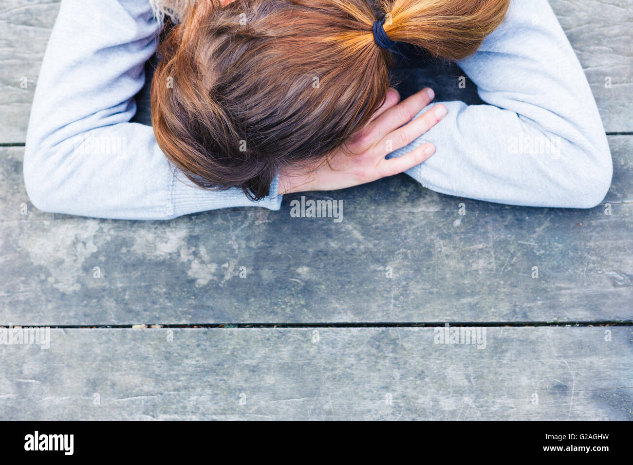 A sad young woman with her head resting on her hands at a table in the park - Stock Image