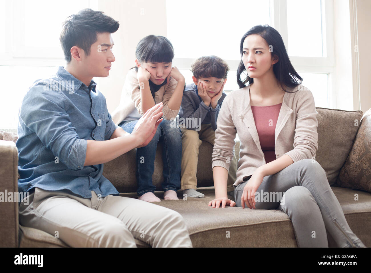 Two children listening to their parents arguing - Stock Image