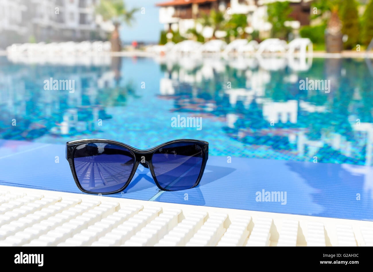 Beautiful sunglasses by the pool lying in the water. - Stock Image