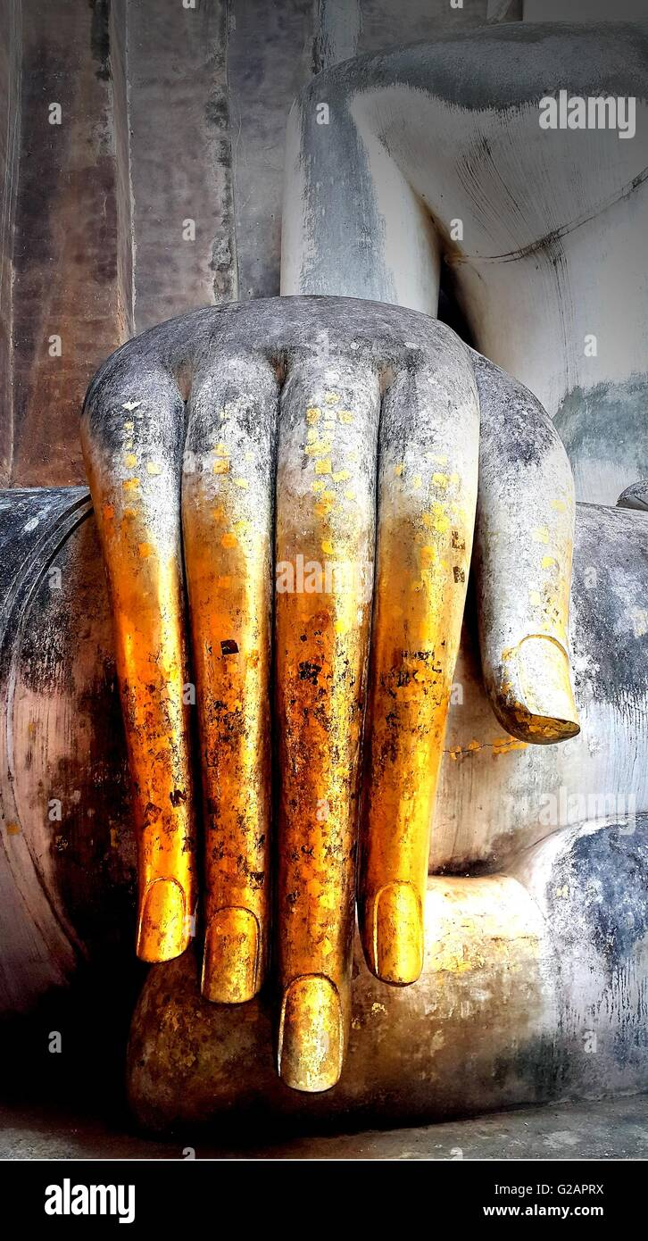 Close up hand of Buddha statue with gold leaf Stock Photo