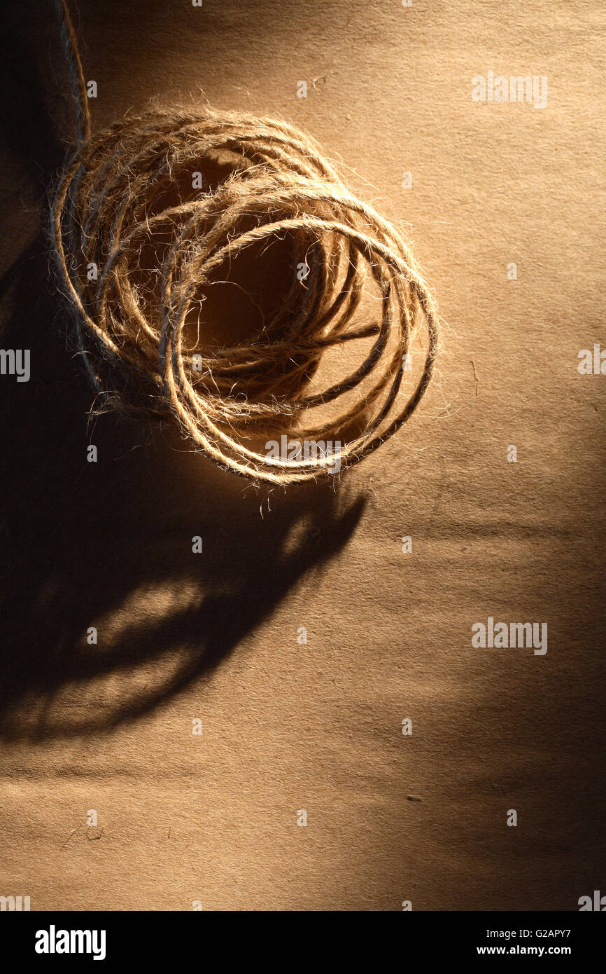 Skein of twine on old brown paper with shadow - Stock Image