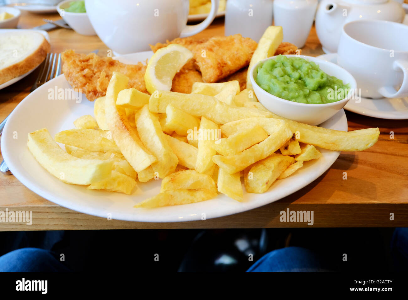 A plate of english fish, chips and mushy peas served on a plate in a restaurant - Stock Image