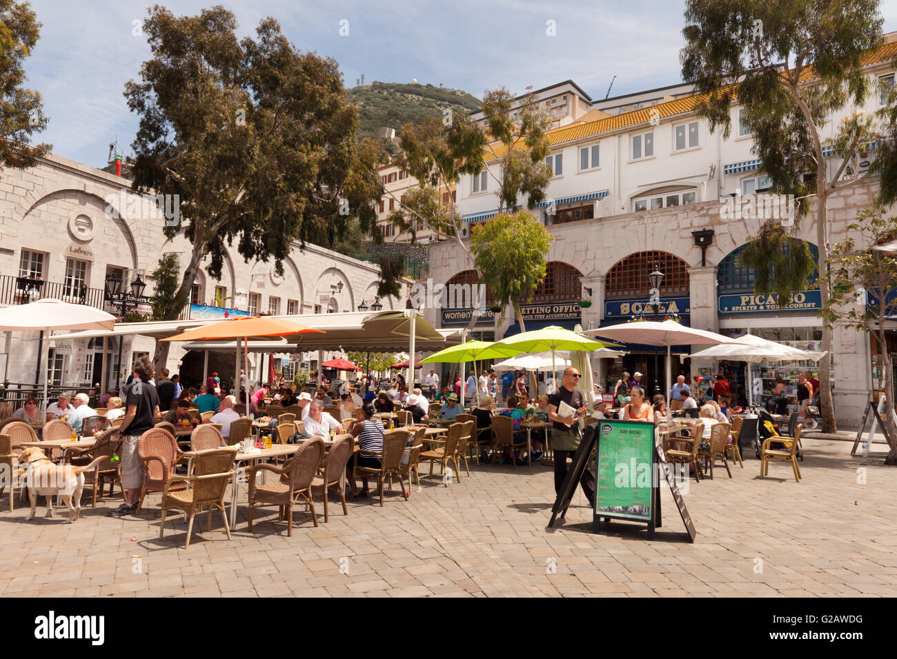 People sitting in cafes on a sunny day in spring, Casemates Square, Gibraltar Europe - Stock Image