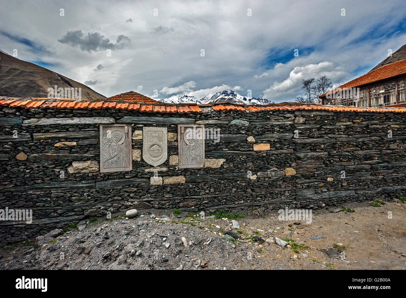 Georgia, the Georgian Military Road , the village of Sno . Stone wall of the village cemetery with images of saints - Stock Image