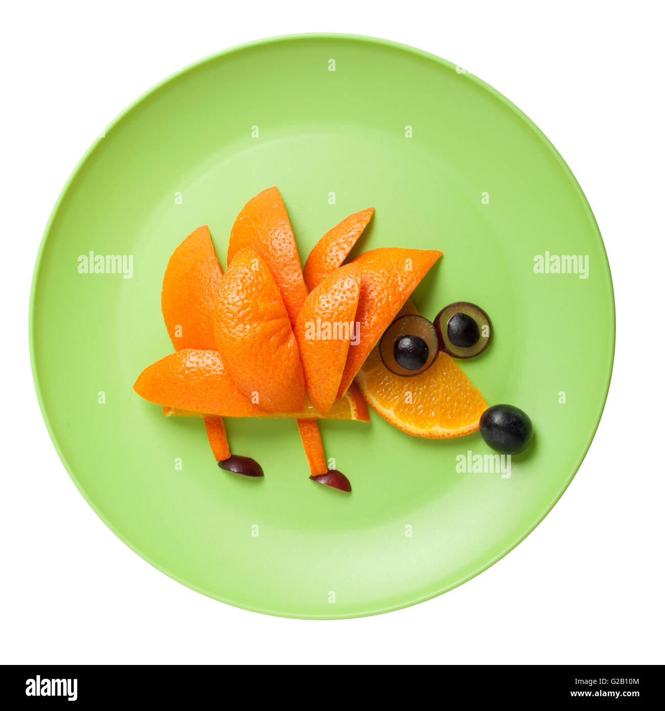 Hedgehog made of orange and grape on green plate - Stock Image