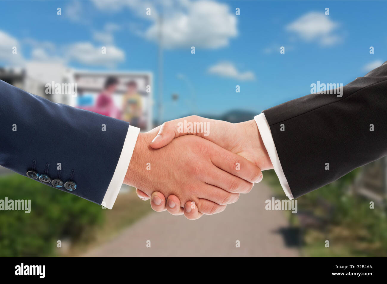 Real estate sale handshake over land and sky background, Sell, buy or partnership concept - Stock Image