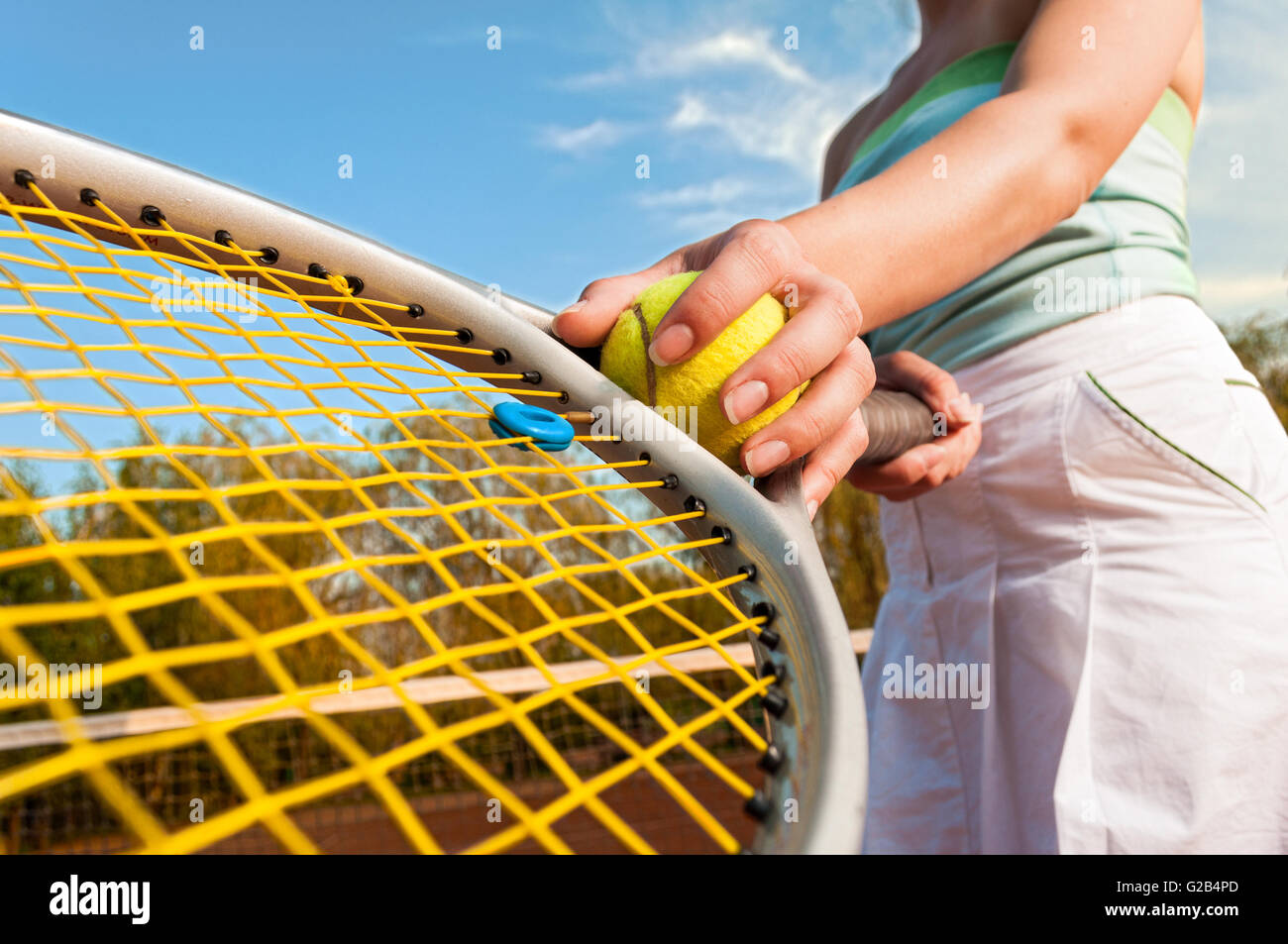 Dynamic tennis concept with female player hand holding ball and racket - Stock Image