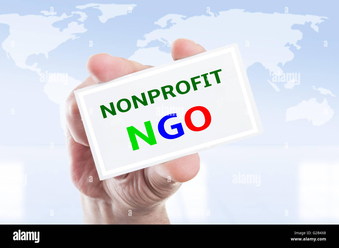Hand holding nonprofit NGO card concept on world map background - Stock Image