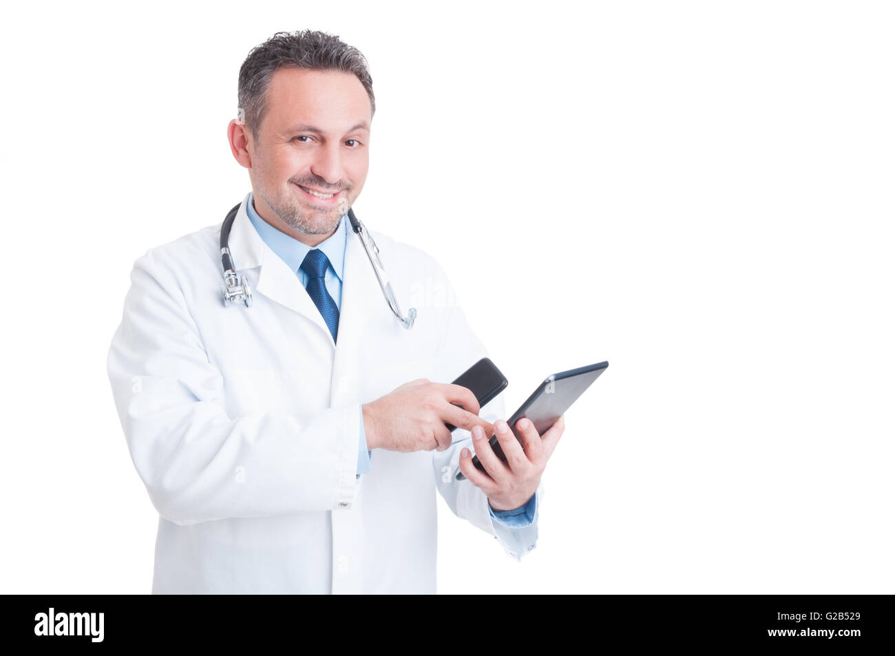 Busy medic or doctor using tablet and phone isolated on white background - Stock Image