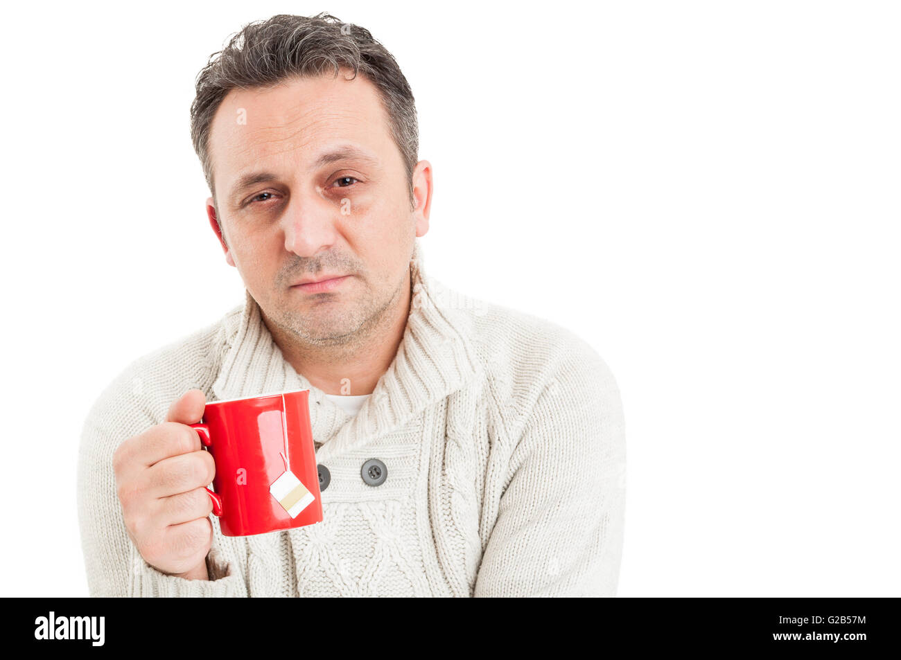 Sick man with sad face suffering of flu virus holding a cup of hot tea - Stock Image