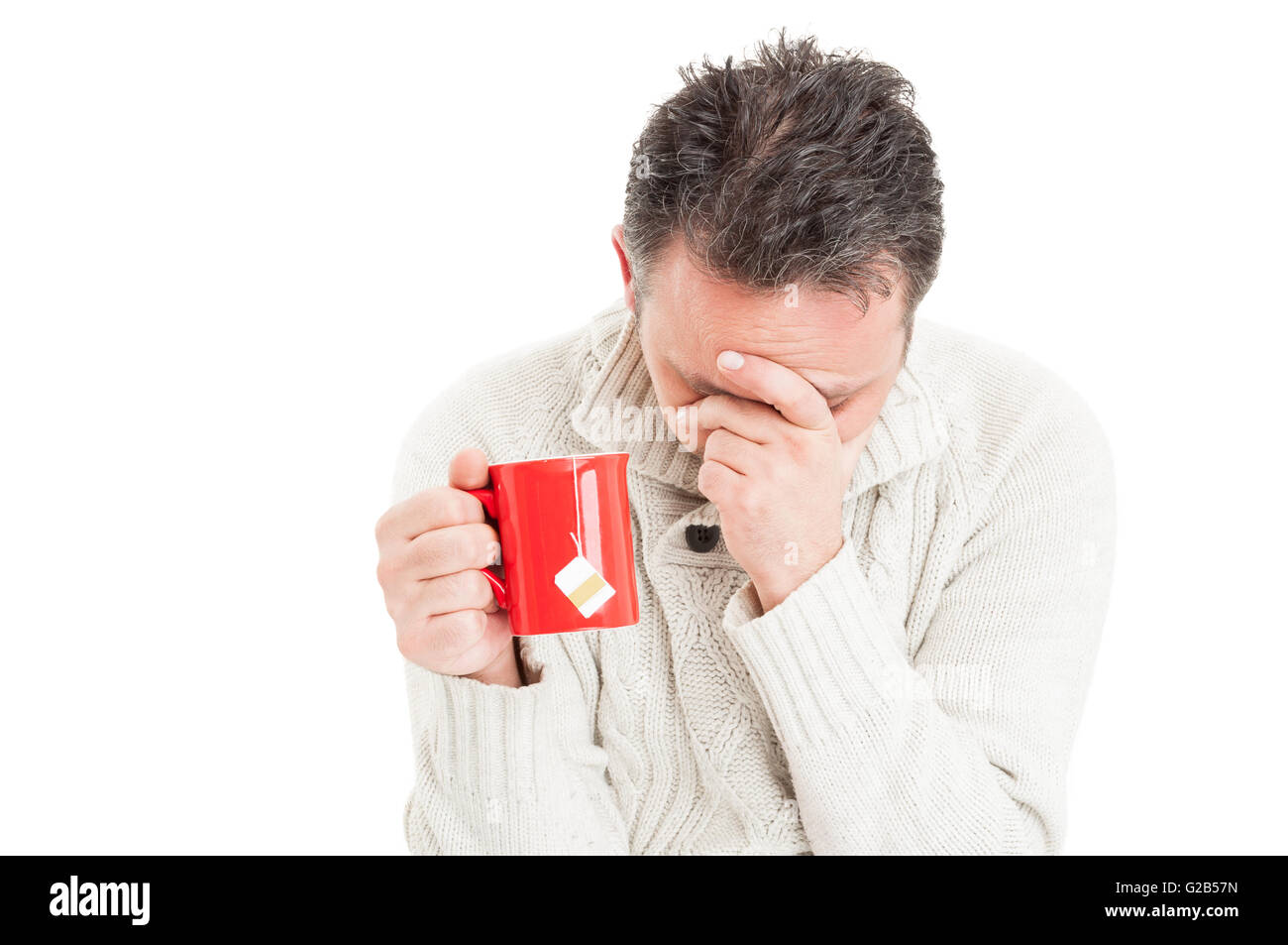 Tired man suffering of flu virus holding a cup of hot tea - Stock Image