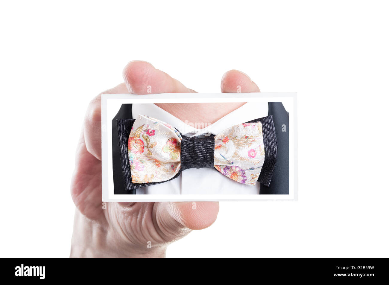 Hand holding card with bowtie picture as bow tie fashion concept - Stock Image
