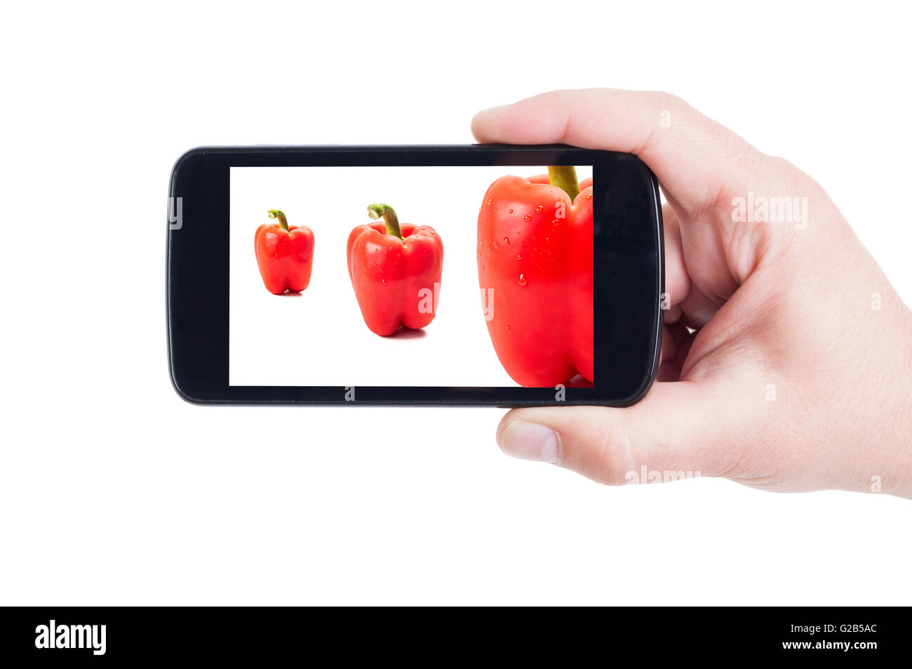 Red peppers on smartphone display or cellphone screen - Stock Image