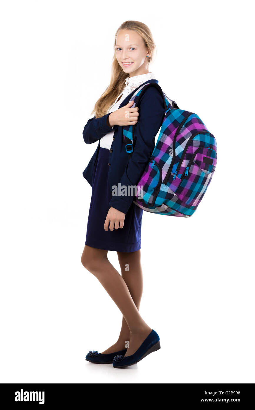 Happy cute beautiful blond schoolgirl wearing school uniform, holding checkered backpack with textbooks, posing - Stock Image