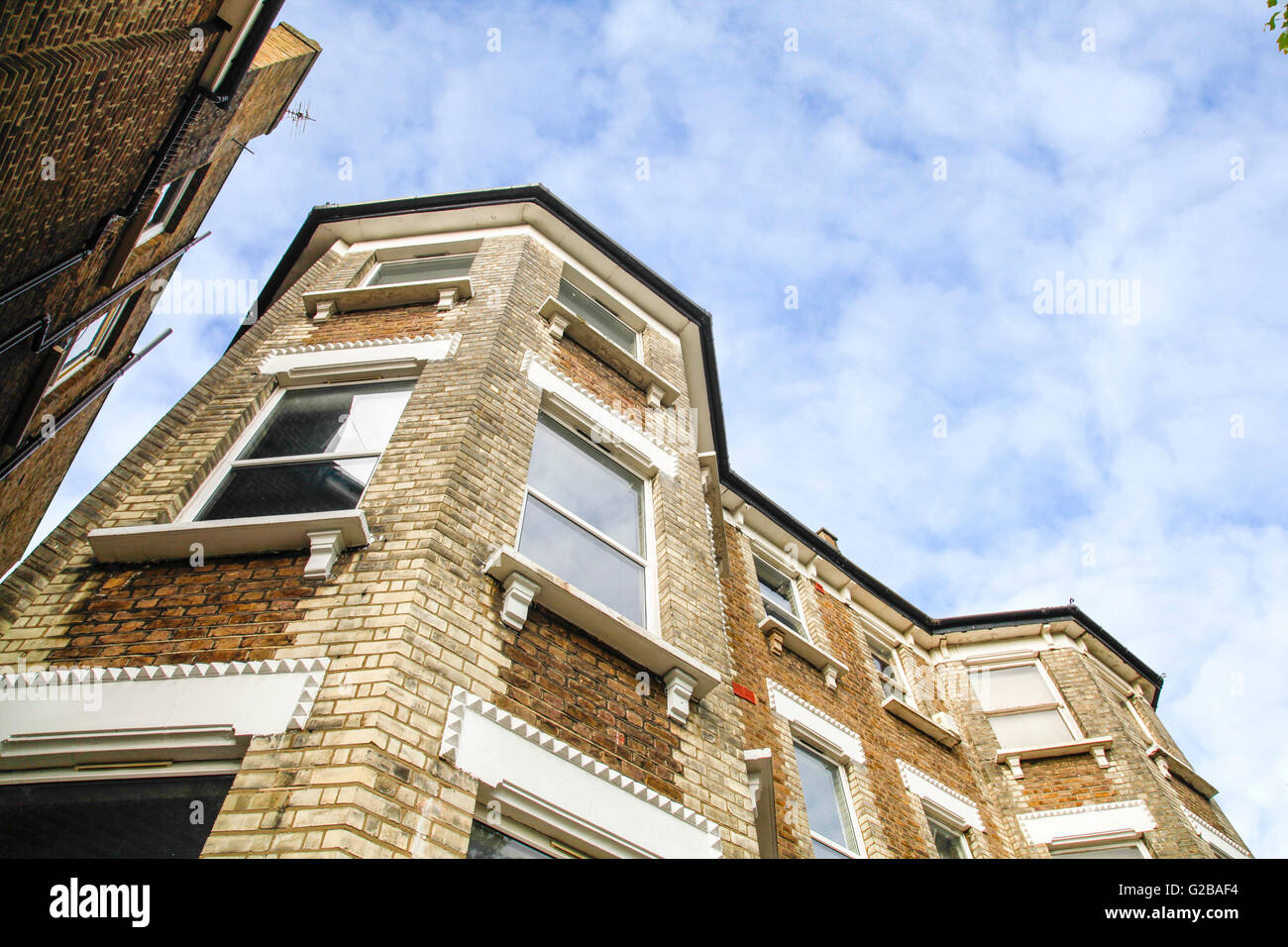 Fordwych Road, West Hampstead. Angled view looking up an exterior wall of an apartment building. Brick walls. - Stock Image