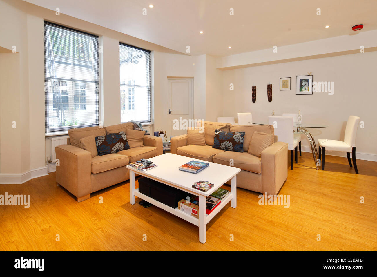 Harrington Gardens. Open plan living and dining area. Neutral toned couches with white coffee table. Modern table - Stock Image