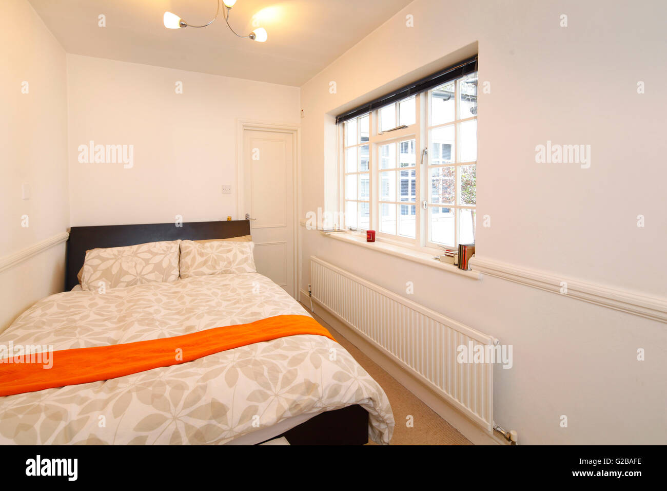 Harrington Gardens. Small Bedroom With Minimal Furniture. Large Window And  Long Radiator On Wall.
