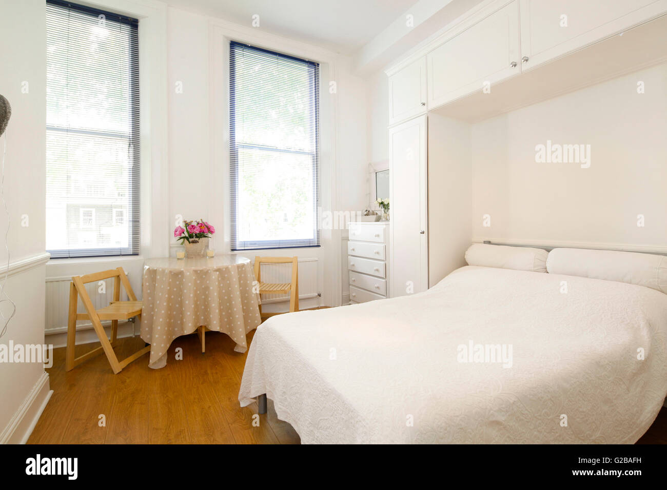 Harrington Gardens. View Of A Bedroom With Retro, Vintage Decor And  Furniture. White Linen On The Bed. Minimal Decoration.