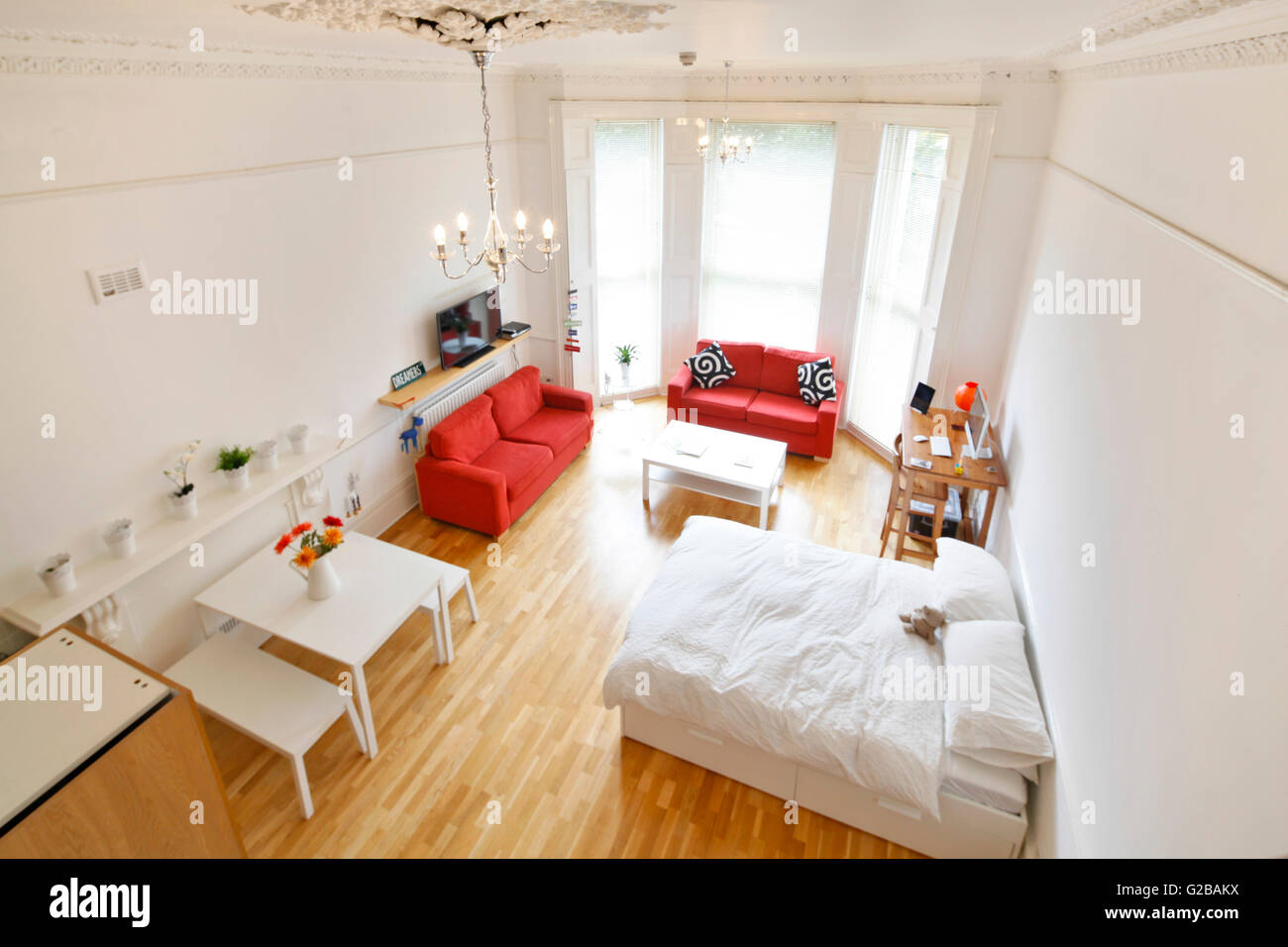 Pembridge Square, Notting Hill. View of a spacious, contemporary studio apartment with a bed with white linen and - Stock Image