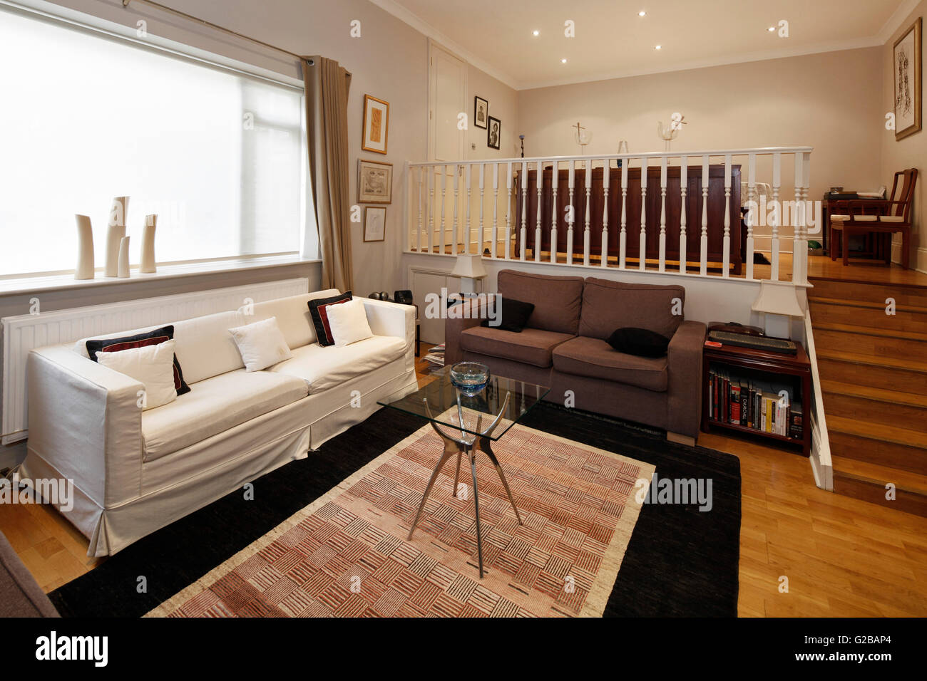 Walden House, Marylebone High Street. View of a two level living room. Stair case with white railing. Contemporary - Stock Image