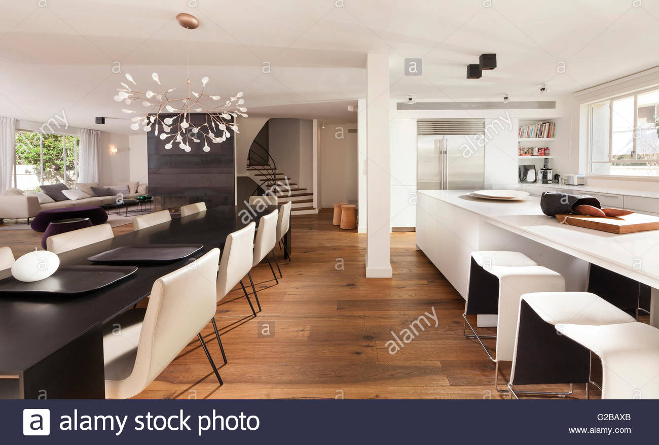 Modern Open Plan Kitchen And Dining Area. Contemporary Furniture In Black  And White. Wood Floors And Staircase In View.
