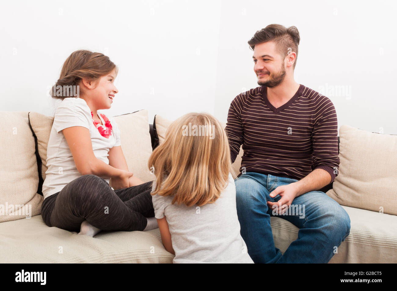 Family time with young father and beautiful daughters in the living room - Stock Image
