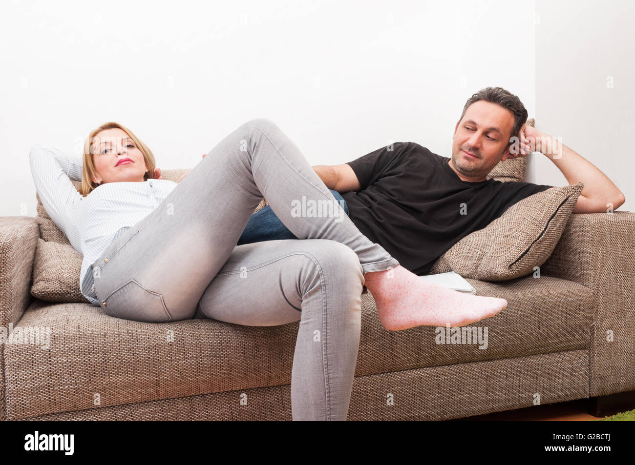 Couple sitting on the couch or sofa after a dispute. Upset wife and husband at home concept - Stock Image