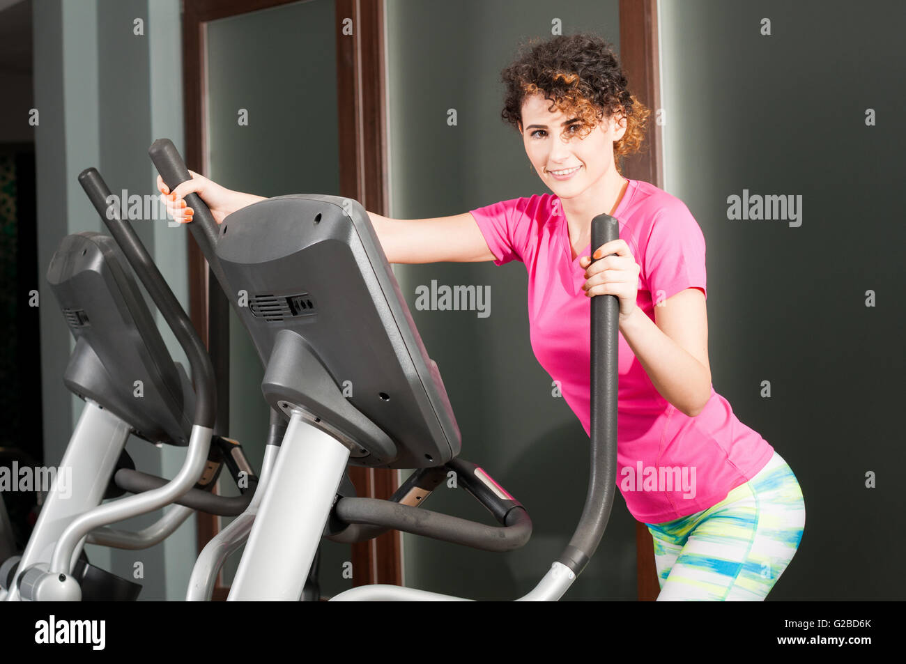 Beautiful athletic woman doing cardio exercises on stepper as resistance concept - Stock Image