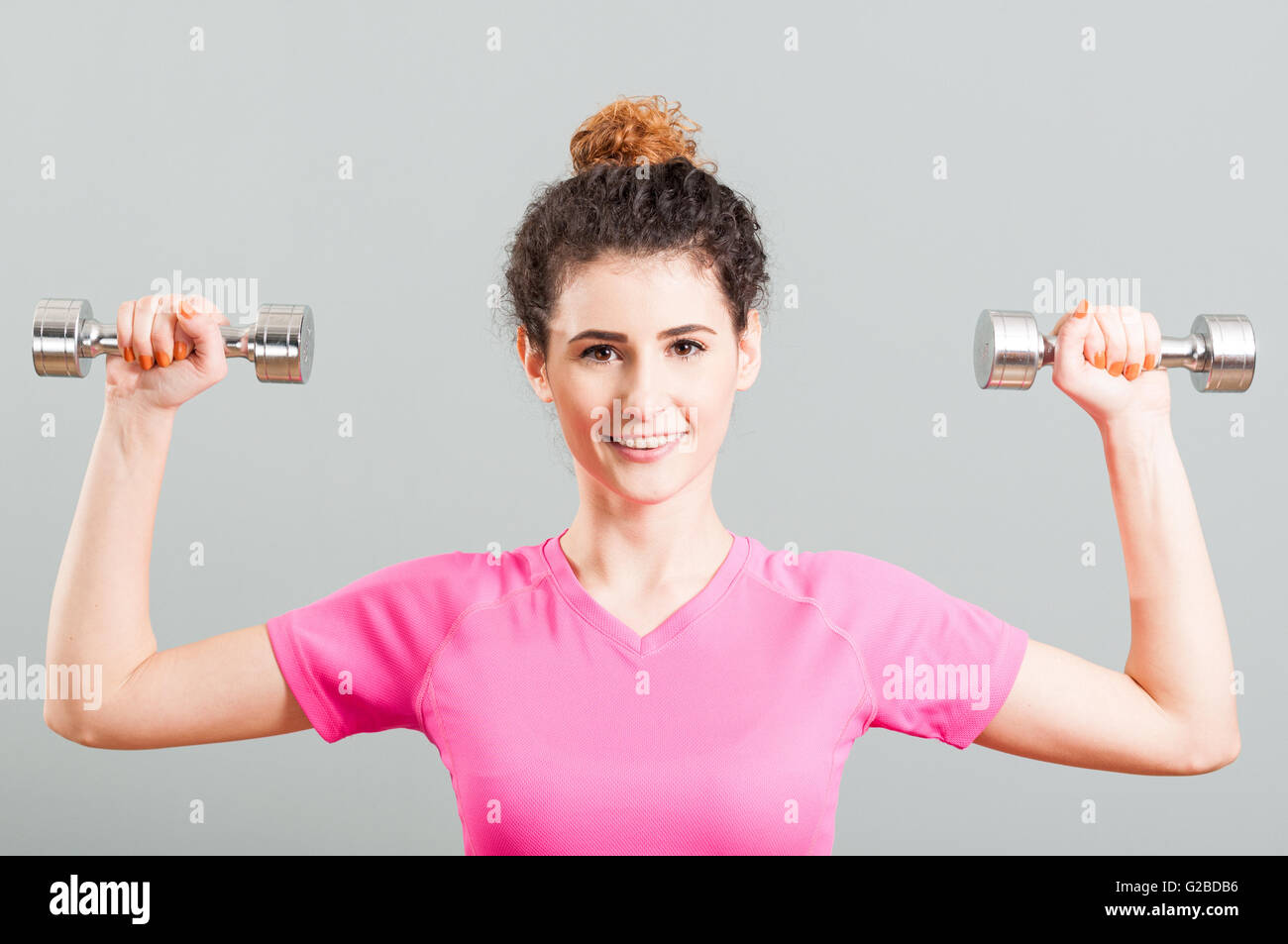 Young smiling woman exercising for deltoid with dumbells in the gym as healthy lifestyle concept Stock Photo