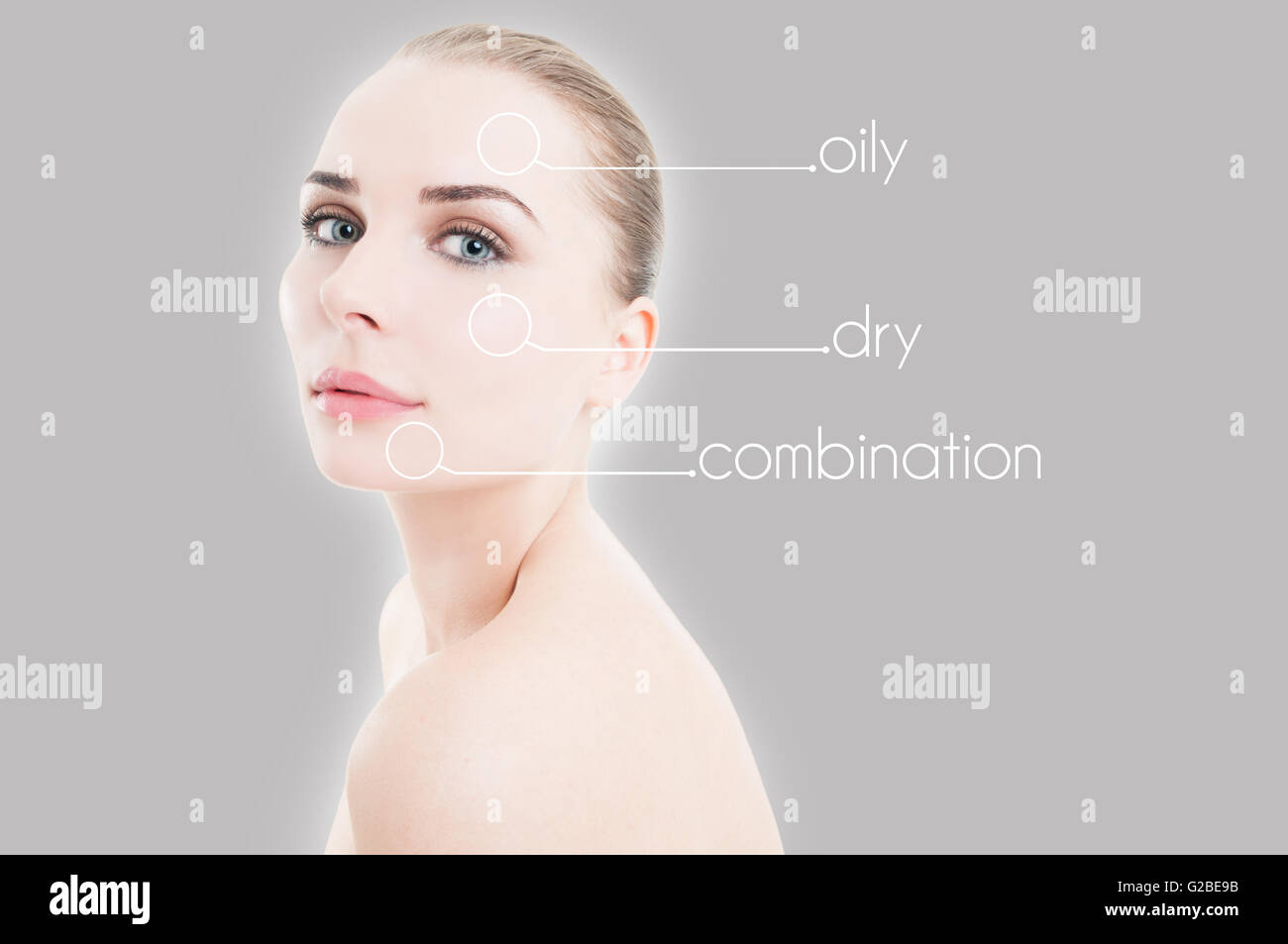 Young attractive female with indicators on her face as cosmetology concept against gray background - Stock Image