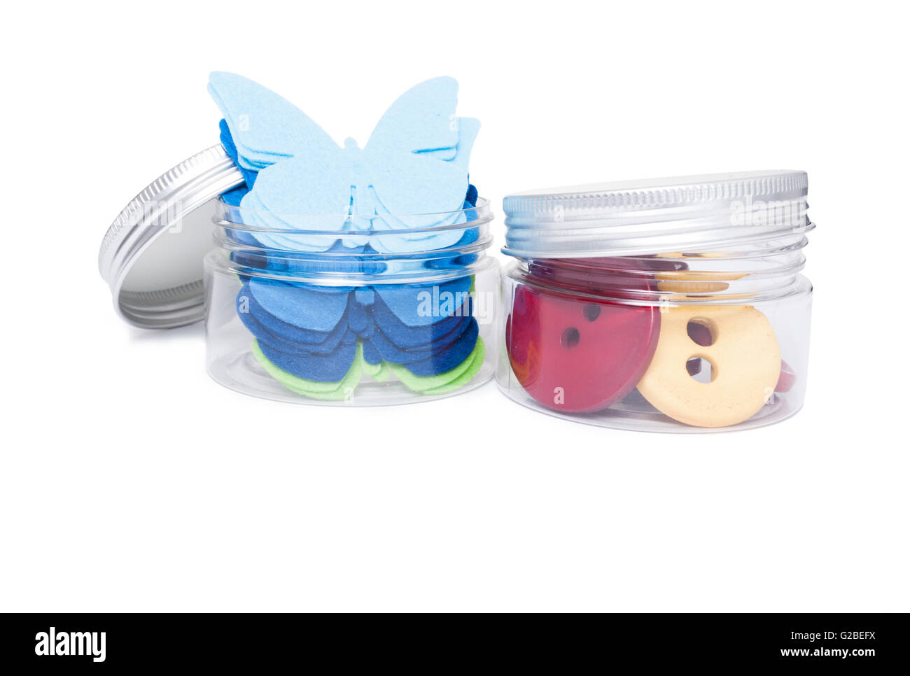 Buttons and butterfly textile shapes as creativity concept in transparent plastic jars isolated on white background - Stock Image