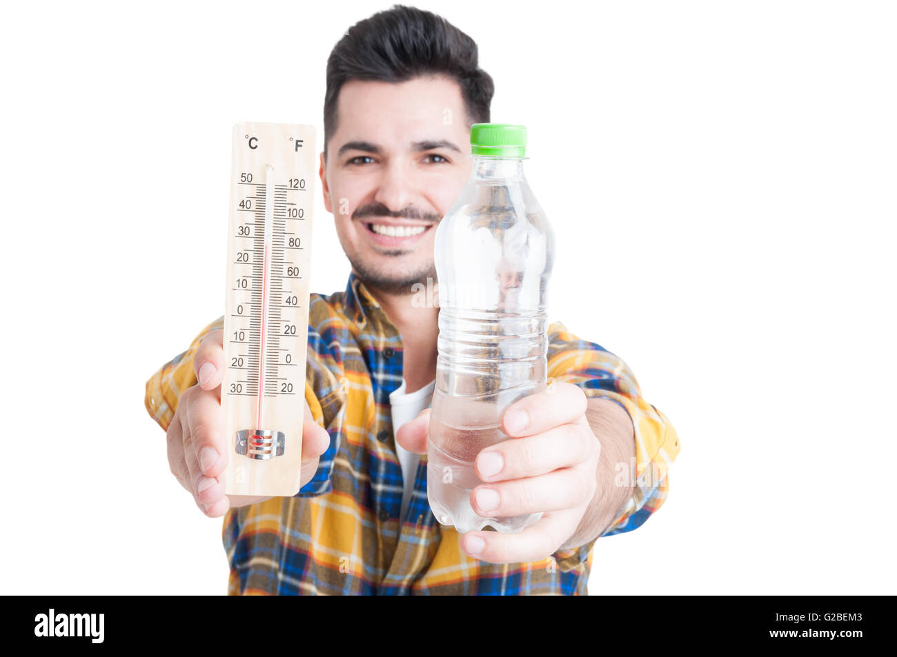 Smiling male holding a bottle of water and a thermometer in his hand as refreshing and vitality concept isolated - Stock Image