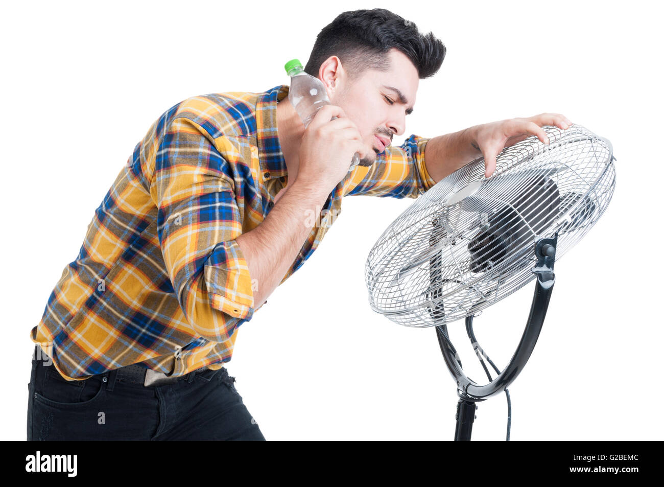 Sweaty and thirsty man standing near fan and cooling off on hot summer days isolated on white background - Stock Image