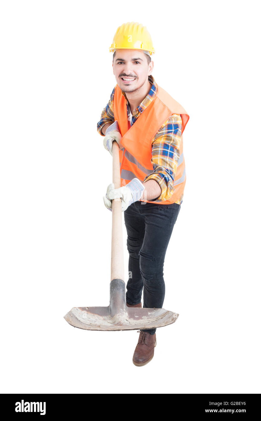 Digging concept with young engineer and shovel acting cheerful on white studio background - Stock Image