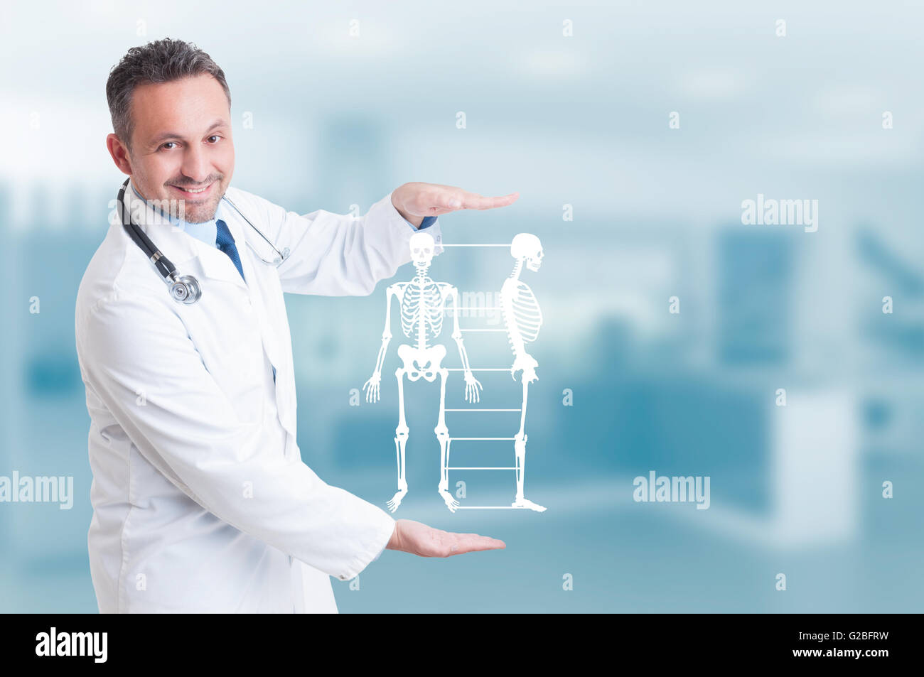 Handsome orthopedist doctor holding skeleton model hologram on his hands and smiling as healthy bone concept with - Stock Image