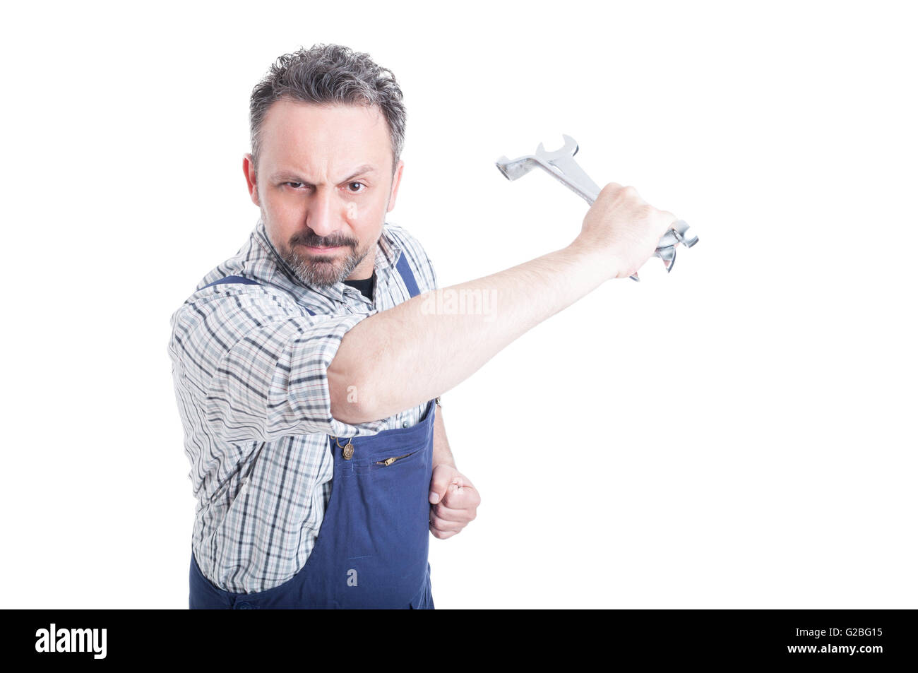 Angry mechanic in workwear acting violent with a steel wrench isolated on white background - Stock Image