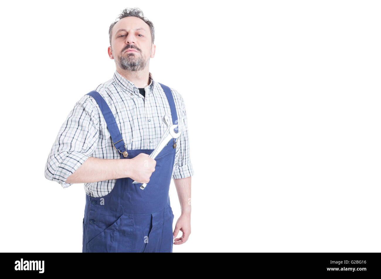 Portrait of attractive male mechanic in blue overalls holding wrench acting like a boos with copyspace isolated - Stock Image