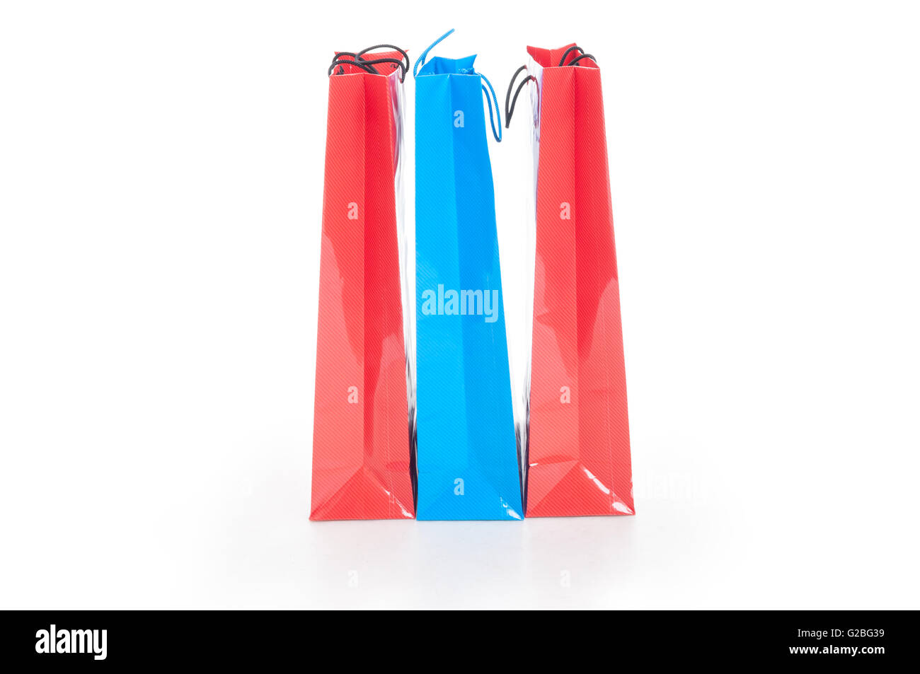 Consumerism and shopping concept with multi colored paper bags isolated on white background - Stock Image