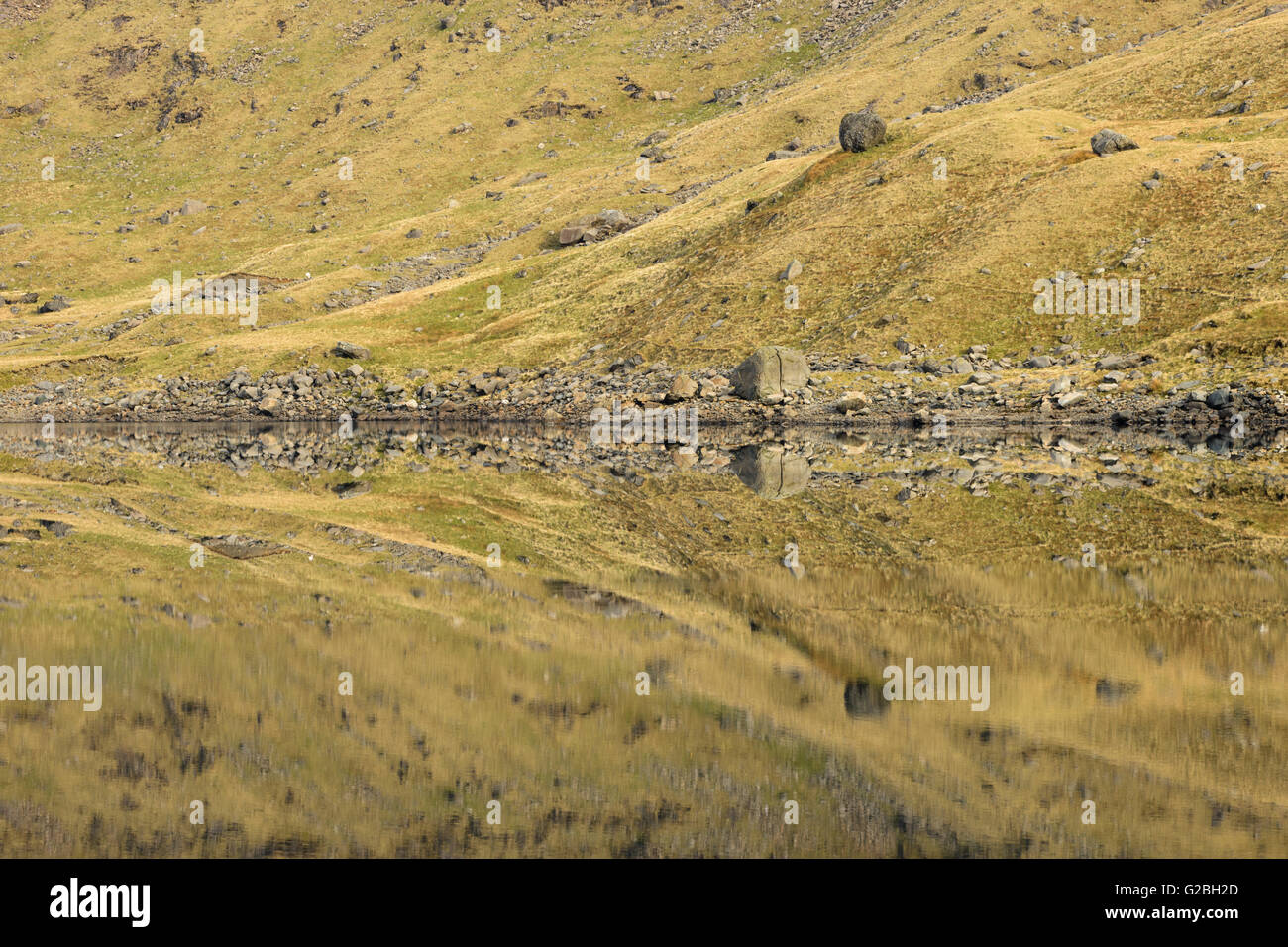 Abstract patterns created by mountainsides reflected in Llyn Llydaw, Snowdonia. - Stock Image
