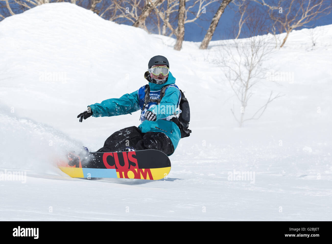 Snowboarder rides steep mountains. Competitions freeride skiers and snowboarders Kamchatka Freeride Open Cup - Stock Image