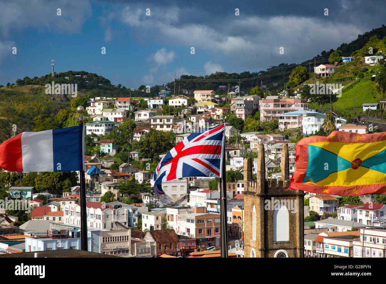 Flags from France, Britain and Grenada fly from Fort George over St Andrews Presbyterian Church and town of St. Georges, Grenada Stock Photo