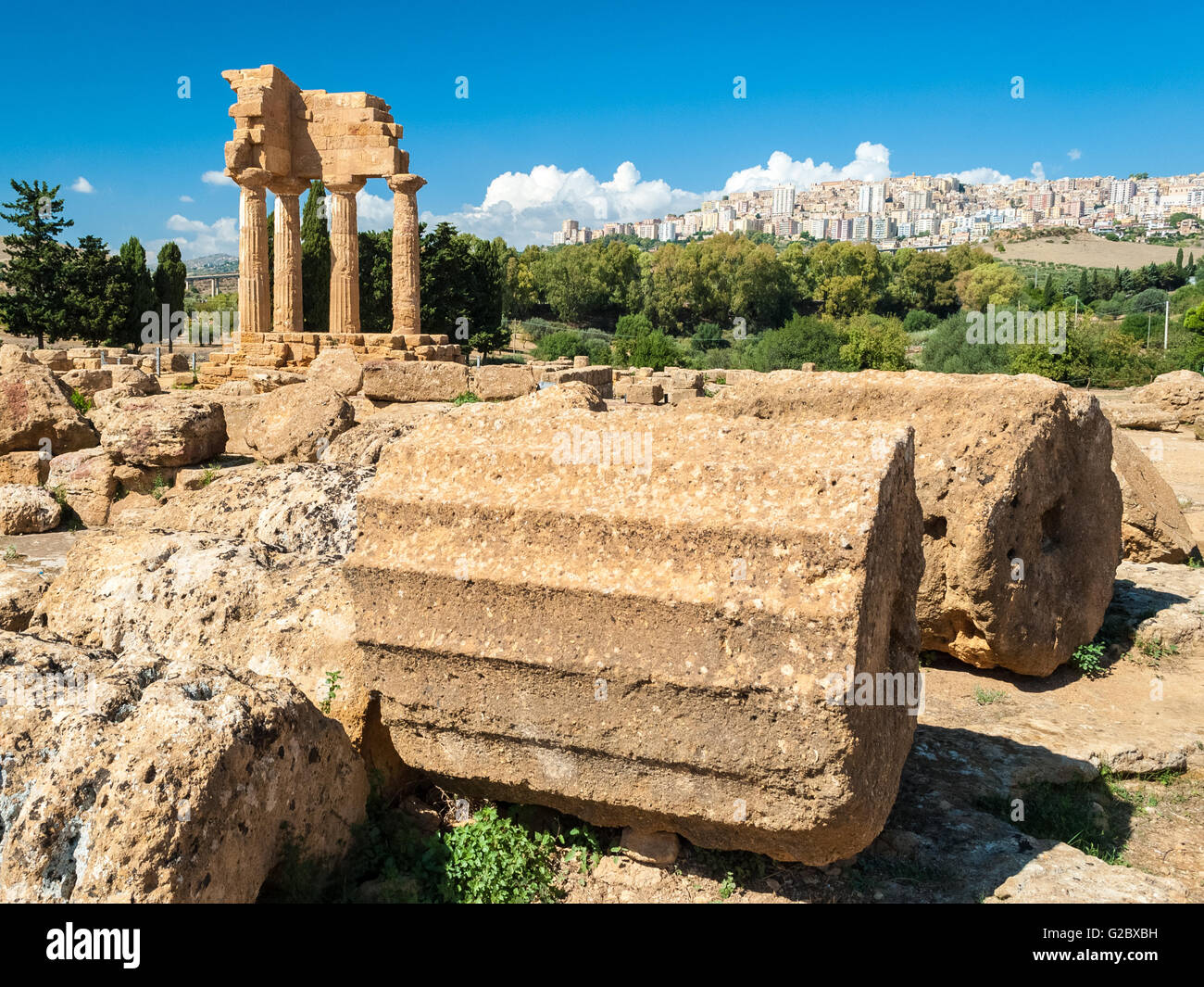 Two big columns in the Valley of the Temples of Agrigento; the temple of Dioscuri in the background - Stock Image